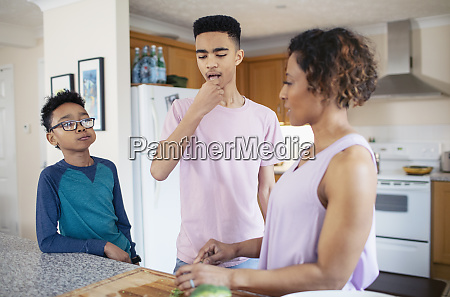 mother and sons cooking in kitchen