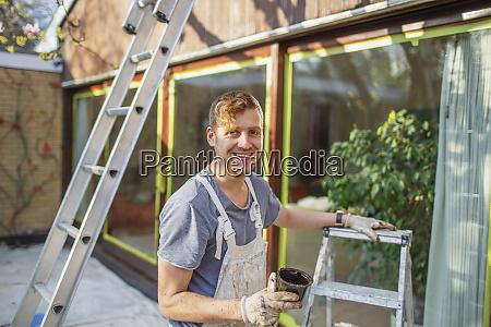 portrait confident male painter with ladder
