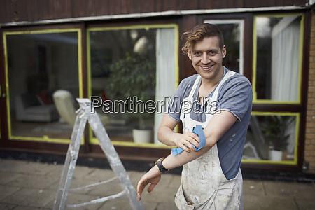 portrait confident male painter outside house