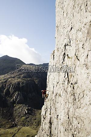 male rock climber scaling large rock