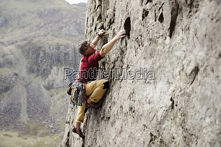 focused male rock climber scaling rock