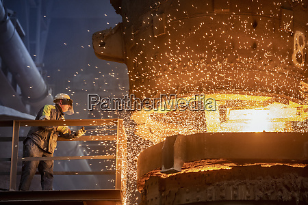 steelworker starting molten steel pour in