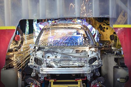 robots welding steel car body in