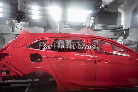 robot paint spraying car bodies in