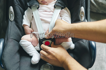 father buckling up baby in baby