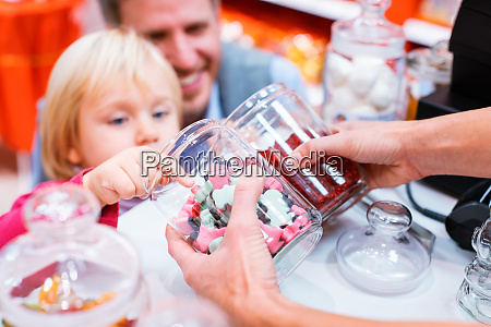 child grabbing some sweets out of