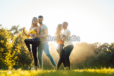 two couples dancing during sunset in