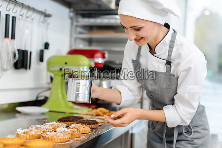patissier putting cocoa powder on little