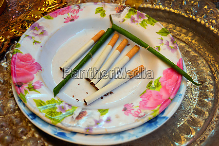 cigarettes and bidis on a plate