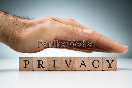 mans hand over the privacy wooden