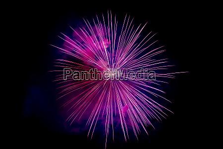 magenta sparkling fireworks background on night