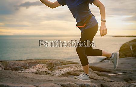 woman runner running at stone beach