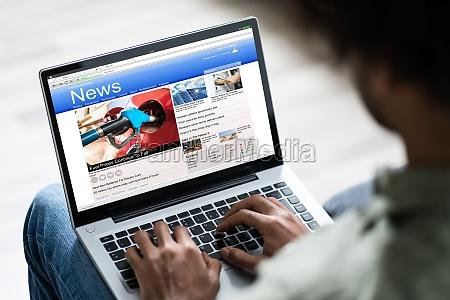 man watching online news on laptop