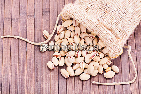 spilled pistachios on wooden background