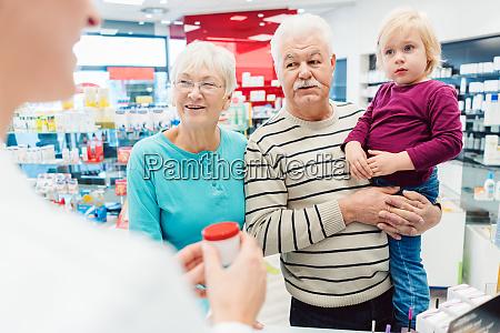 grandparents in pharmacy buying prescription drugs
