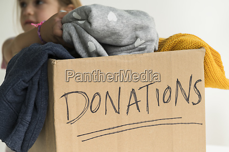 girl putting clothing into donations box