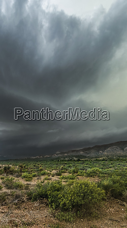 dramatic dark storm clouds over scrubland