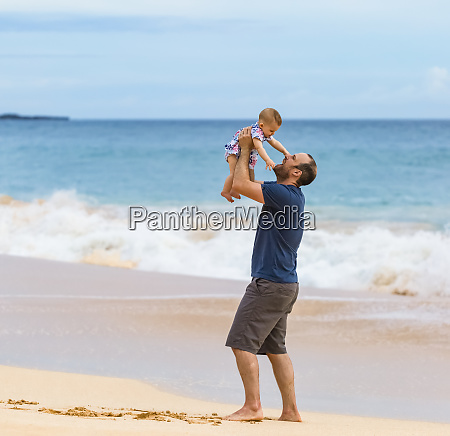 father holds his baby daughter in