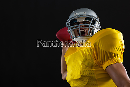 energetic american football player holding a