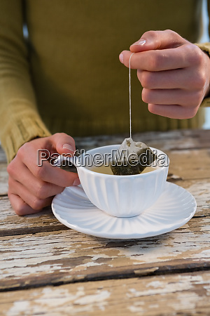 mid section of woman dipping tea