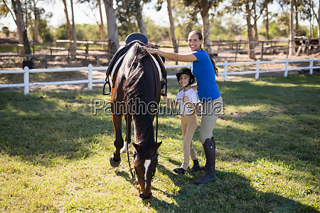 portrait of siblings standing by horse