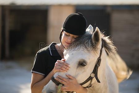 female jockey embracing horse at barn
