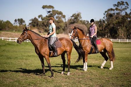 young women horseback riding