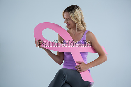 smiling woman holding breast cancer awareness