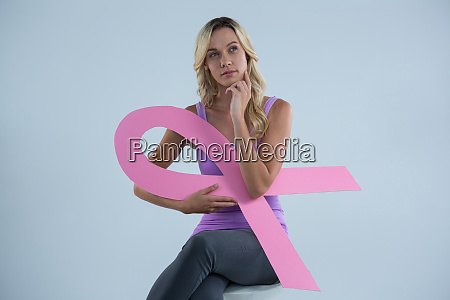 thoughtful woman with breast cancer awareness
