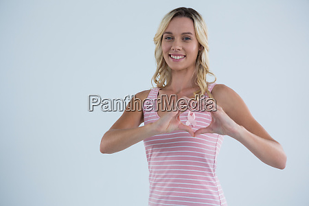 portrait of smiling woman making heart