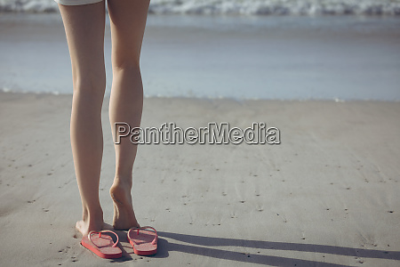 woman standing barefoot on sand at