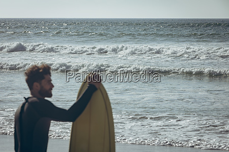 male surfer with a surfboard standing