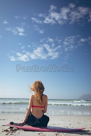 female surfer sitting on surfer board