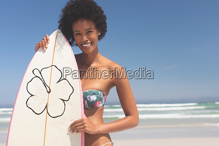 female surfer with a surfboard standing