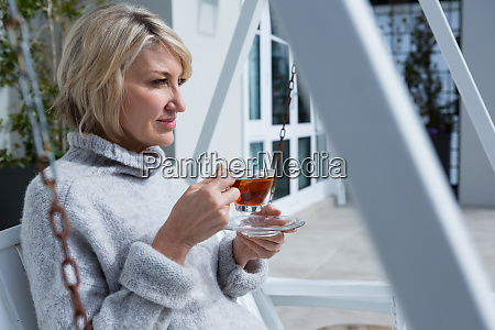 thoughtful woman having lemon tea in