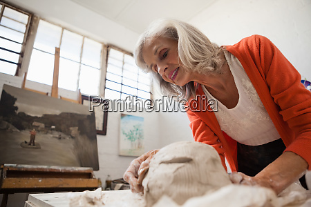attentive senior woman shaping a molded