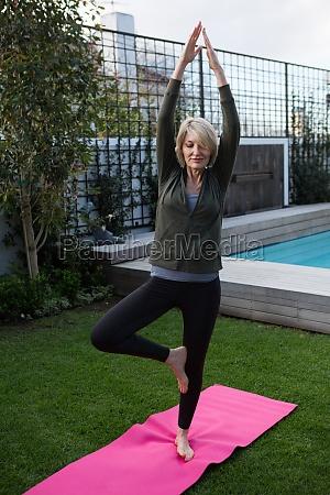 beautiful woman practicing yoga in lawn