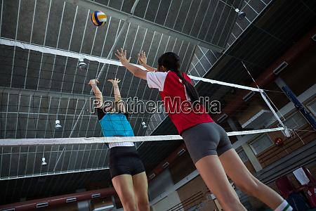 female players playing volleyball in the