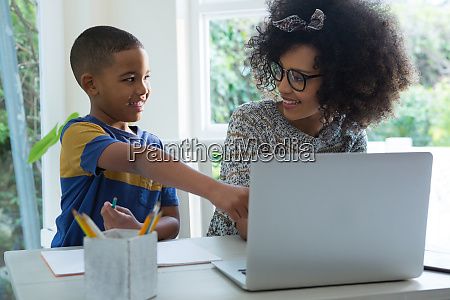 son doing homework while mother using