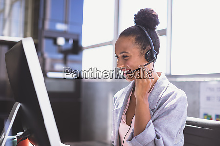 businesswoman talking on headset while working