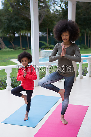 mother and daughter performing yoga in