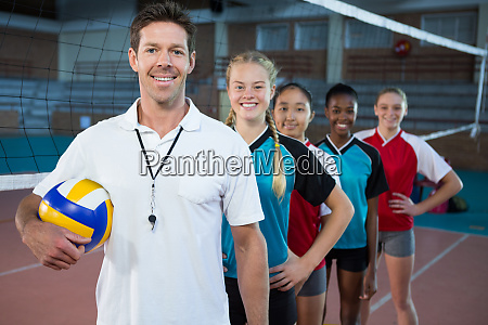 male coach and volleyball players standing