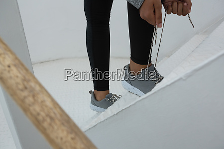 female athlete tying shoelace on steps
