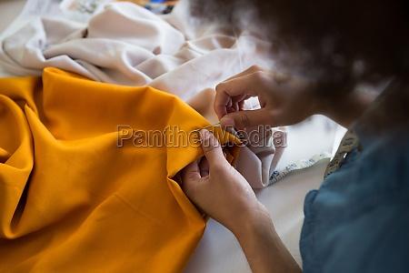 female fashion designer stitching cloth with