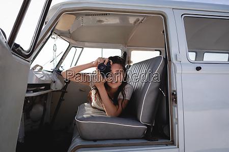 beautiful woman capturing photo with digital