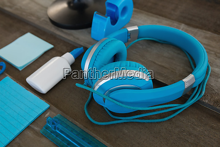 headphone and various stationery on wooden