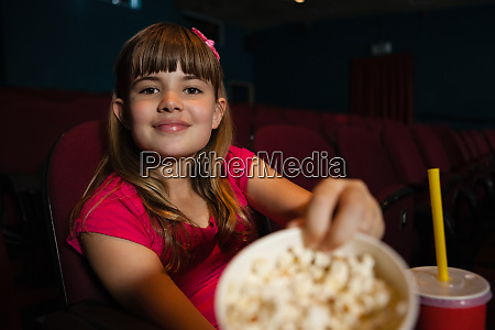 portrait of girl showing popcorn container