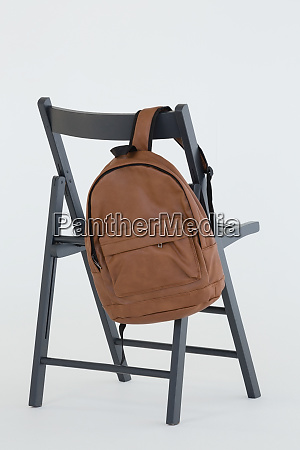 backpack hanging on black chair
