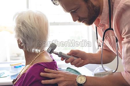 male dermatologist examining senior patient through
