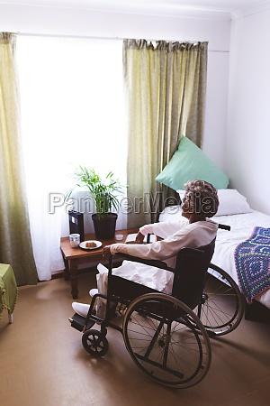 thoughtful senior woman sitting on wheelchair